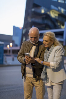 Spain, Barcelona, senior couple sharing cell phone in the city at dusk - MAUF02267