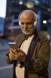 Spain, Barcelona, senior man with headphones and cell phone in the city at dusk - MAUF02270