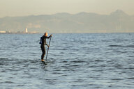 Spain, Andalusia, Tarifa, man stand up paddle boarding on the sea - KBF00361