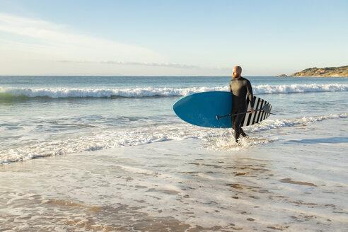Spain, Andalusia, Tarifa, man walking with stand up paddle board at the sea - KBF00367