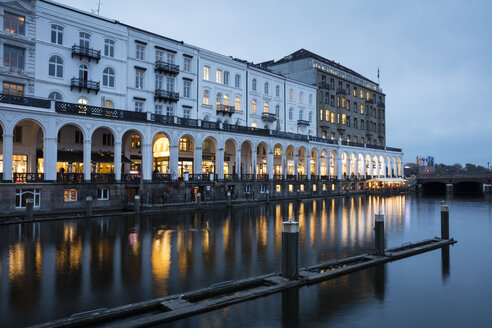 Germany, Hamburg, lighted arcades with Binnenalster in the foreground at dusk - WIF03717