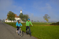 Germany, Pilgrimage Church St. Coloman and couple of cyclists on tour - LBF02333