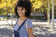 Portrait of a smiling woman, standing in a park - GIOF05302