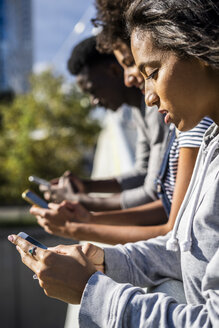 Friends standing side by side, using smartphones - GIOF05326