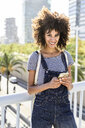 Young woman standing on a bridge, holding smartphone - GIOF05335