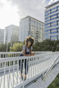 Young woman standing on a bridge, using smartphone, with headphones around her neck - GIOF05356