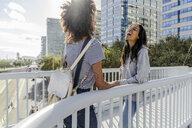Girl friends meeting on a bridge, having fun - GIOF05362