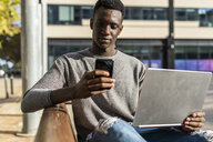 Young man sitting on a bench in the city, using laptop and smartphone - GIOF05386