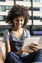 Mid adult woman with curly hair, sitting on a bench, using digital tablet - GIOF05395
