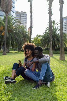 Happy couple sitting on lawn in a park, using smartphone - GIOF05413