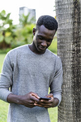 Young man leaning on tree trunk in a park, using smartphone - GIOF05428