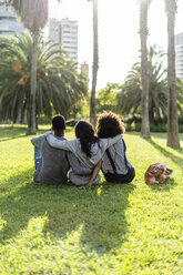 Three friends sitting in a park, watching the sunset - GIOF05431