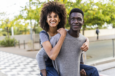 Young man carrying his girlfriend piggyback in the street - GIOF05437