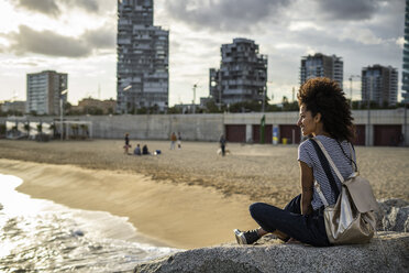 Young woman relaxing on the beach, sitting on rocks, rear view - GIOF05446