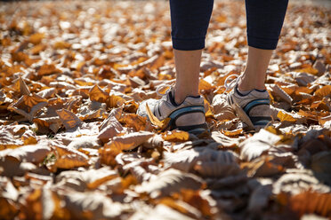 Close-up of spotive woman standing in autumn leaves - CHPF00528