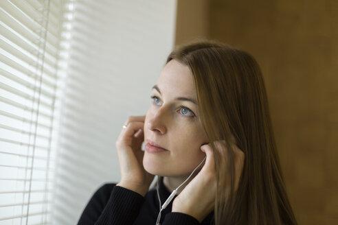 Portrait of woman near window putting on earphones - VGF00151