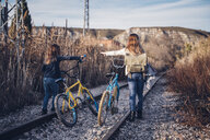 Two girls walking on the train track with bicycles - OCMF00186