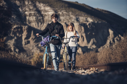 Boy and girl walking on the train track with bicycles - OCMF00192