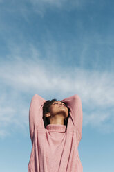 Relaxed young woman wearing pink turtleneck pullover enjoying fresh air - LOTF00031