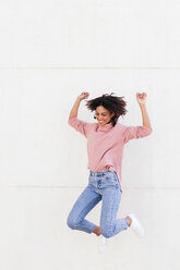 Happy young woman jumping in the air against light background - LOTF00037