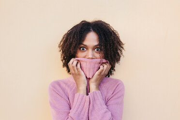 Young woman with afro hair covering her face with a pink turtleneck jumper and showing surprise. Studio shot. - LOTF00040