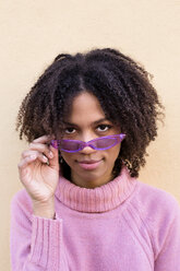 Mixed race woman with afro hair, pink sweater and purple sunglasses. Studio shot. - LOTF00043
