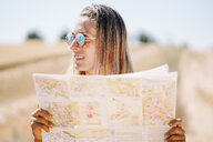 Blond young woman wearing mirrored sunglasses holding map looking at distance - OCMF00199