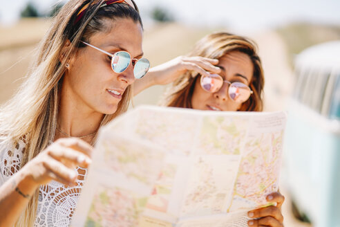 Two young women on roadtip orientating with map - OCMF00202