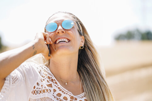 Laughing blond young woman on the phone wearing mirrored sunglasses - OCMF00205