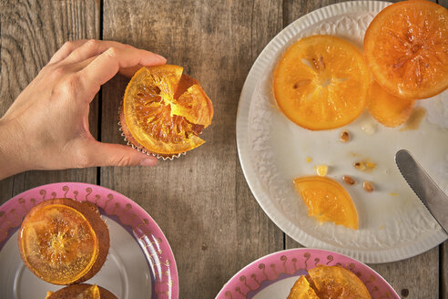 Woman's hand garnishing muffins with candied orange slices - EPF00528