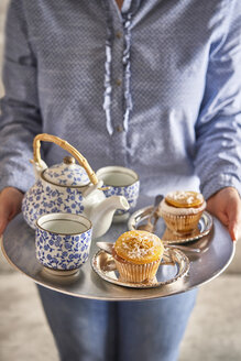 Woman serving fresh muffins and tea on silver platter - EPF00531