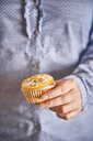 Woman's hand holding muffin with candied orange slice, close-up - EPF00534