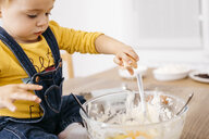 Toddler girl sitting on kitchen table throwing egg into bowl for preparing dough, partial view - JRFF02337