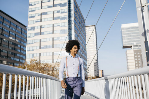 Spain, Barcelona. Afro man walking through the city with skyscrapers in the background - JRFF02401