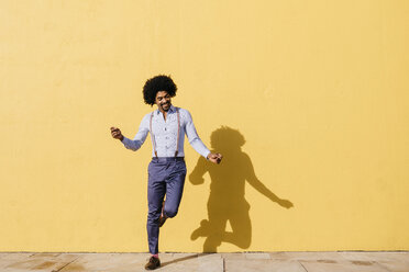 Smiling man dancing in front of yellow wall - JRFF02413