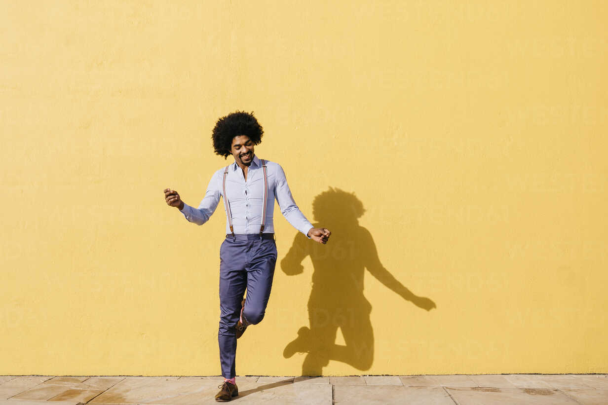 Smiling man dancing in front of yellow wall - JRFF02413 - Josep Rovirosa/Westend61