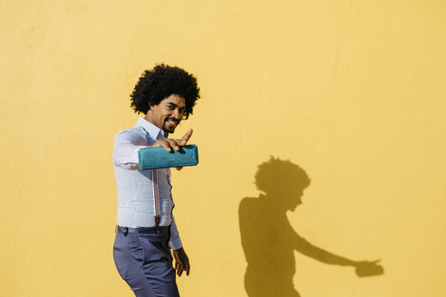 Smiling man with loudspeaker listening music and dancing in front of yellow wall - JRFF02416