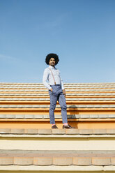 Stylish man standing on stairs - JRFF02422