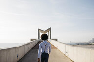Spain, Barcelona, back view of man walking on a bridge - JRFF02428