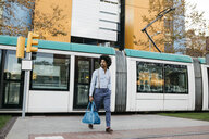 Spain, Barcelona, man with bag crossing the street in front of a tramway - JRFF02437