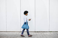 Man with bag walking in front of a white wall while looking at cell phone - JRFF02440