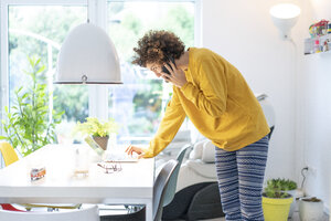 Woman using laptop and cell phone on table at home - JOSF02674