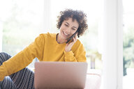 Happy woman using laptop and cell phone at home - JOSF02680