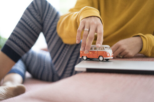 Woman playing with camper van model at home - JOSF02683