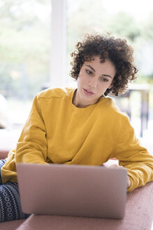 Woman using laptop on couch at home - JOSF02686