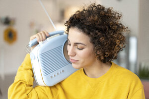 Woman listening to music with portable radio at home - JOSF02689