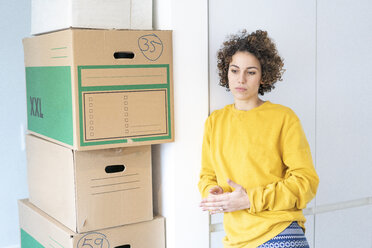Serious woman at home with cardboard boxes - JOSF02692