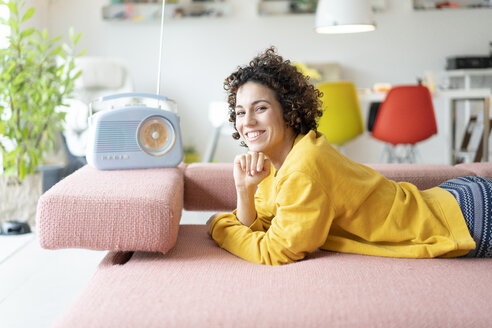 Portrait of happy woman lying on couch listening to music with portable radio at home - JOSF02701