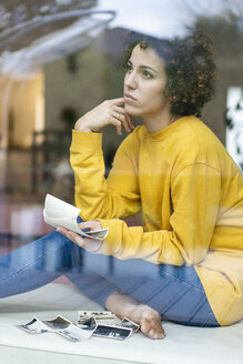 Serious woman sitting behind window at home holding photos - JOSF02719