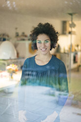 Portrait of smiling woman standing behind window at home - JOSF02731